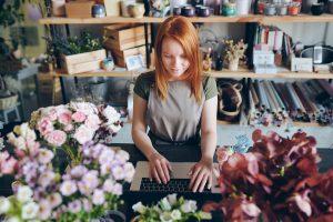 Image d'une femme fleuriste qui publie sur les réseaux sociaux ses photos